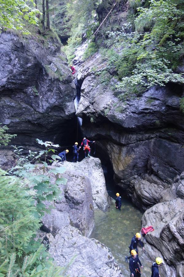 Zwei der Canyoning-Gruppen in der Starzlachklamm: Oben kurz vorm Abseilen durch den Wasserfall; mitte und unten beim Nochmalreinspringen vom Felsen.